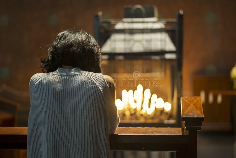 Femme chrétienne priant dans l'église photo libre de droits