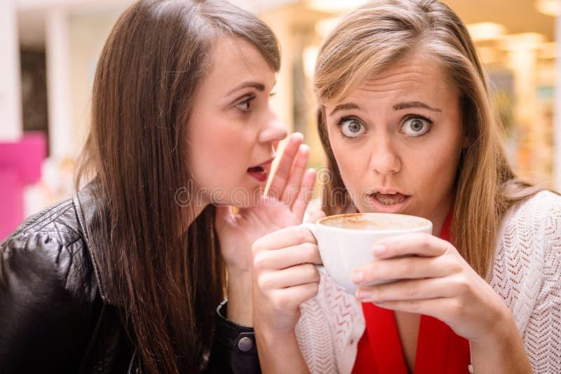 Femme chuchotant dans des ses oreilles d'amis image stock