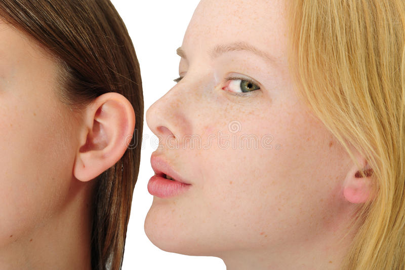 Femme chuchotant dans l'oreille de friend´s photos stock