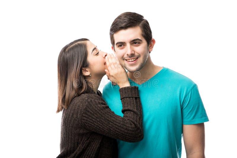 Femme chuchotant dans l'oreille du `s d'ami images libres de droits