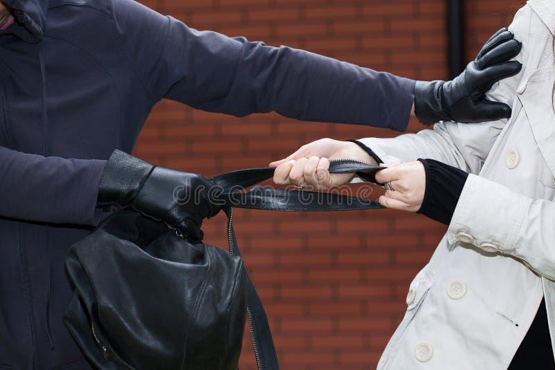 Femme combattant avec un voleur image stock