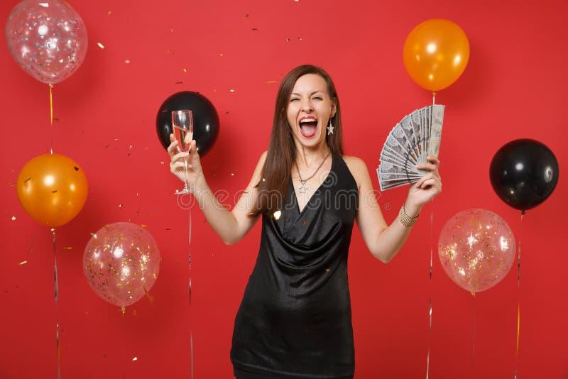 Femme comblée dans la célébration criarde de robe noire tenant un bon nombre de paquet de dollars, argent d'argent liquide, verre photo libre de droits