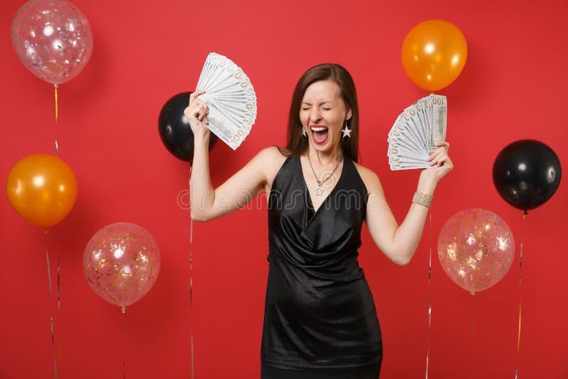 Femme comblée dans peu de robe noire criant, célébration, tenant un bon nombre de paquet de dollars, argent d'argent liquide sur  image stock