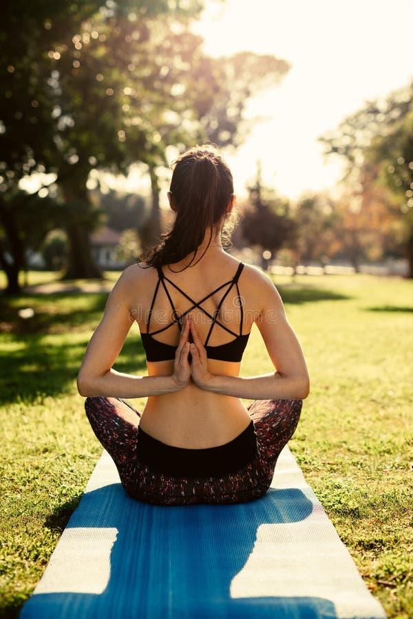 Femme commettant le yoga inverse de position de prière images stock