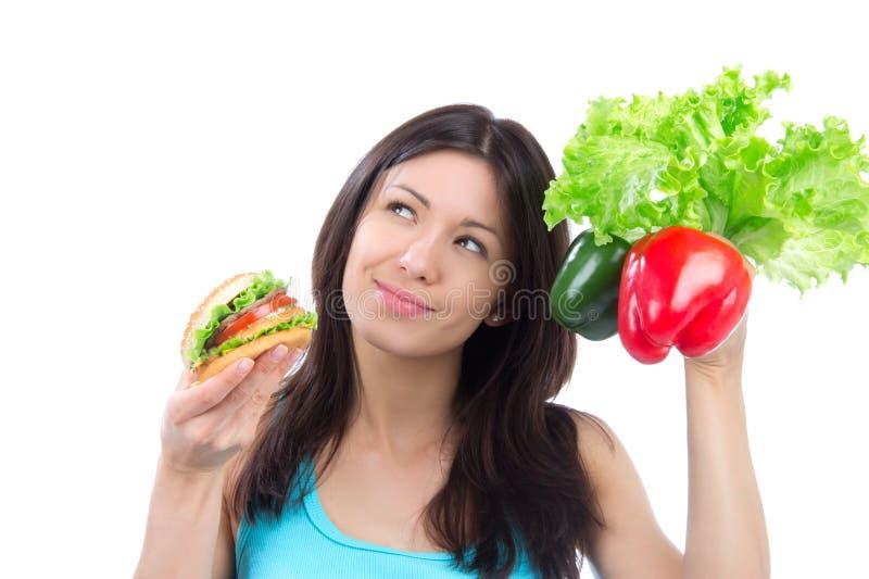 Femme comparant l'hamburger et la salade fraîche de poivrons photos libres de droits