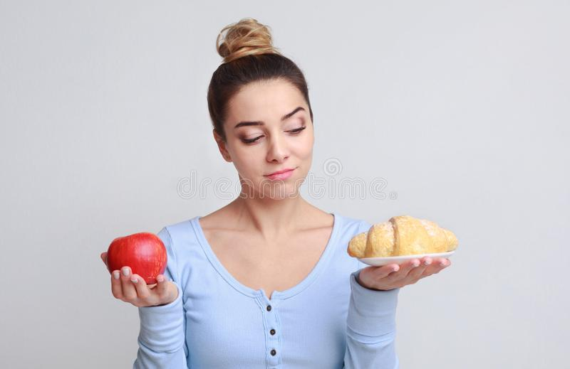 Femme comparant le croissant et la pomme rouge au-dessus du fond images stock