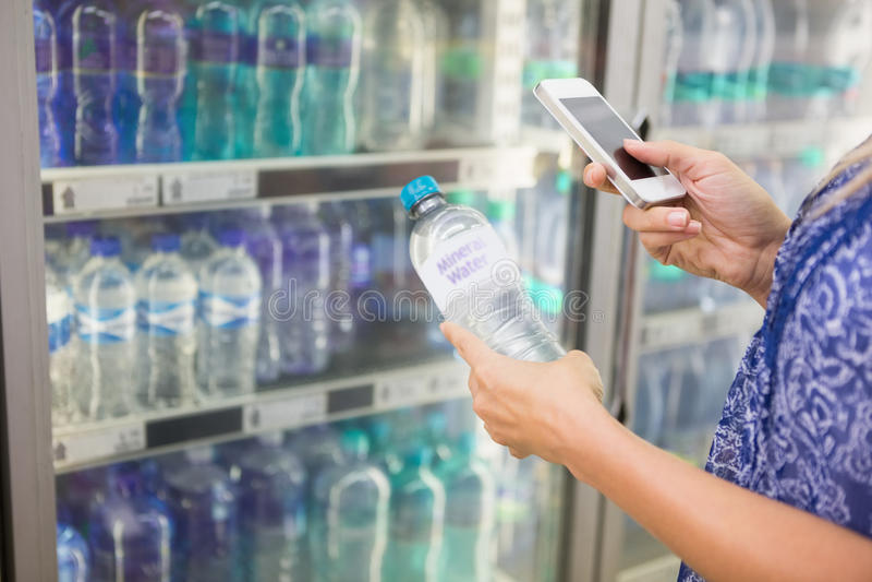 Femme comparant le prix d'une bouteille de l'eau à son téléphone photographie stock
