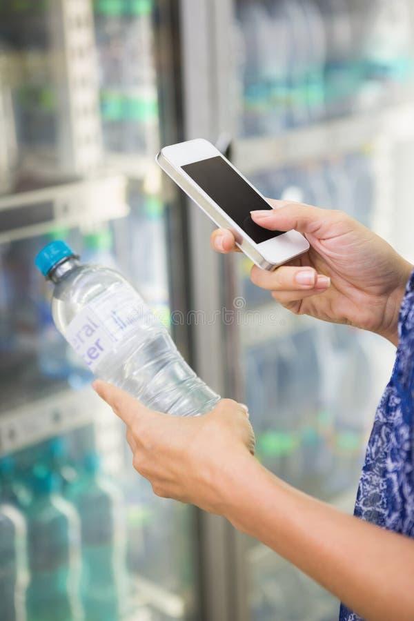 Download Femme Comparant Le Prix D'une Bouteille De L'eau à Son Téléphone Image stock - Image du propriétaire, affaires: 56489499