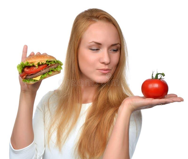 Femme comparant le sandwich malsain savoureux à hamburger à disposition et le toma photographie stock libre de droits