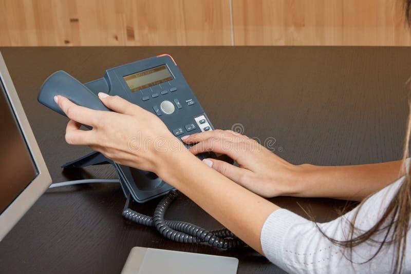 Femme composant à un téléphone photo stock