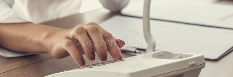 Femme composant un numéro de téléphone au téléphone blanc de ligne terrestre photos libres de droits