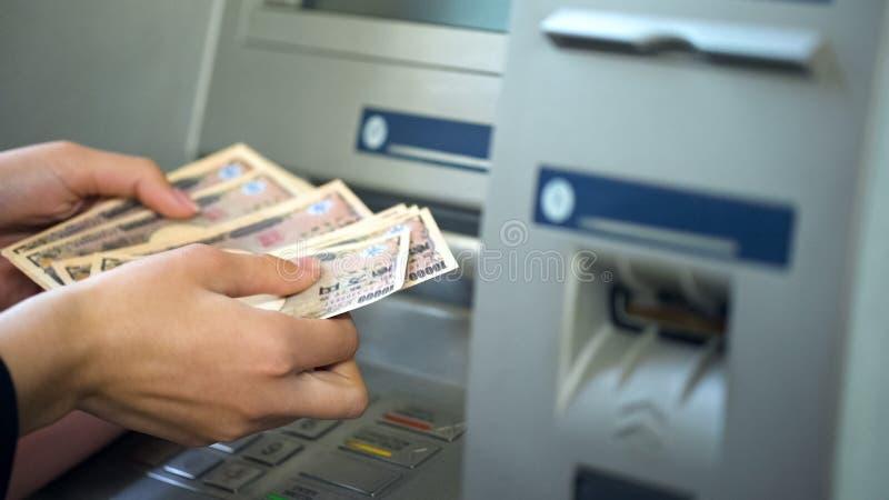 Femme comptant Yens japonais retirés de l'atmosphère, 24 heures de service, opérations bancaires faciles image libre de droits