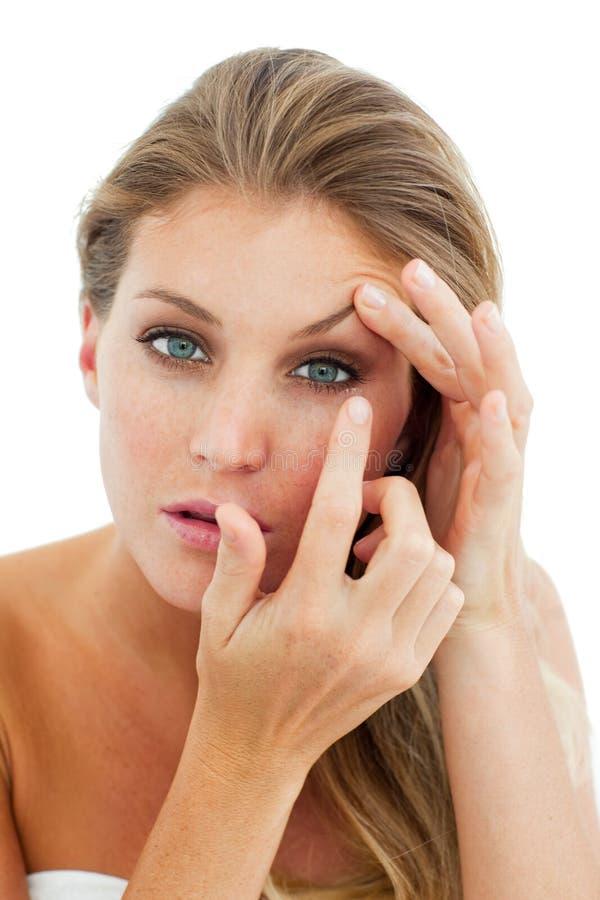 Femme concentré mettant un verre de contact photos stock