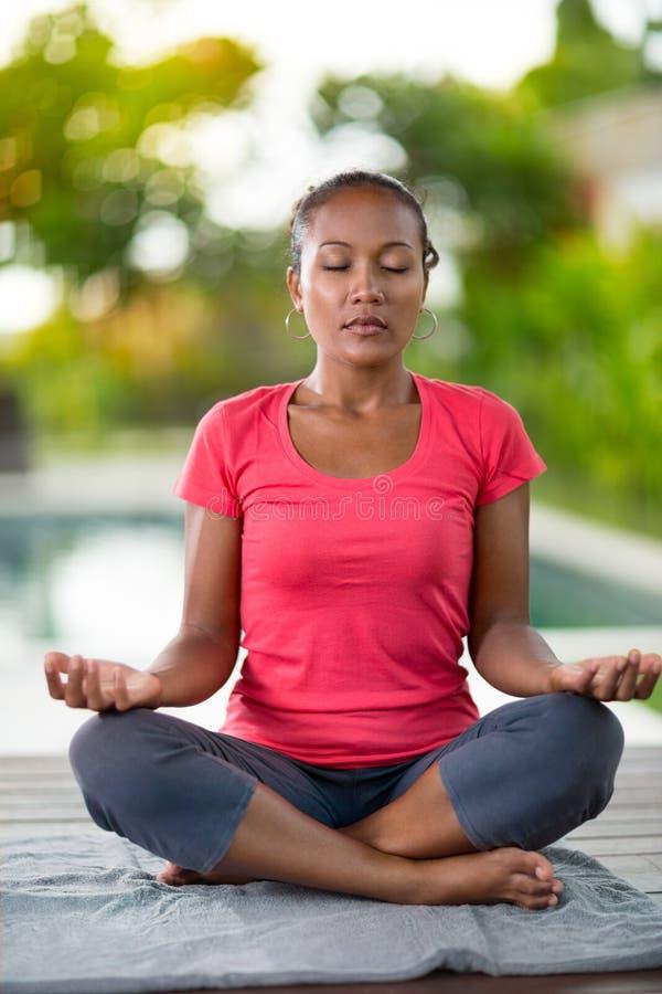 Femme concentrée avec les yeux étroits faisant le yoga images libres de droits