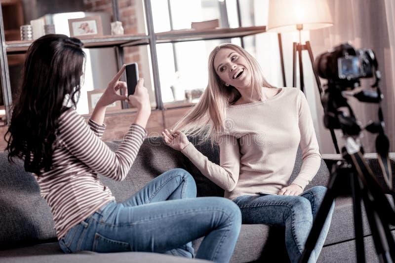 Femme concentrée photographiant son ami photo stock
