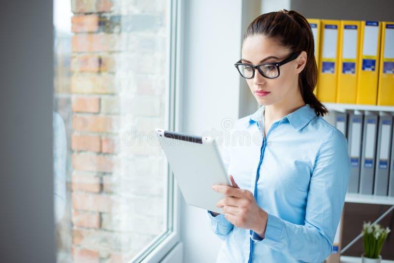 Femme concentrée se tenant près de la fenêtre à son hildin de bureau photos stock