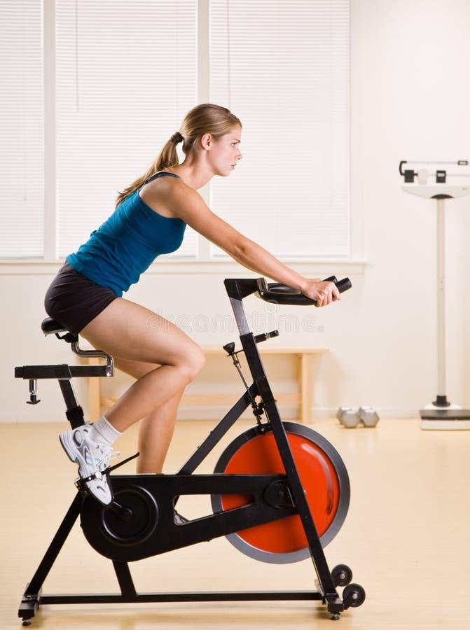 Femme conduisant la bicyclette stationnaire dans le club de santé images libres de droits