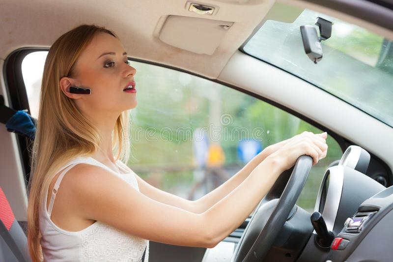 Femme conduisant la voiture avec le casque photographie stock libre de droits