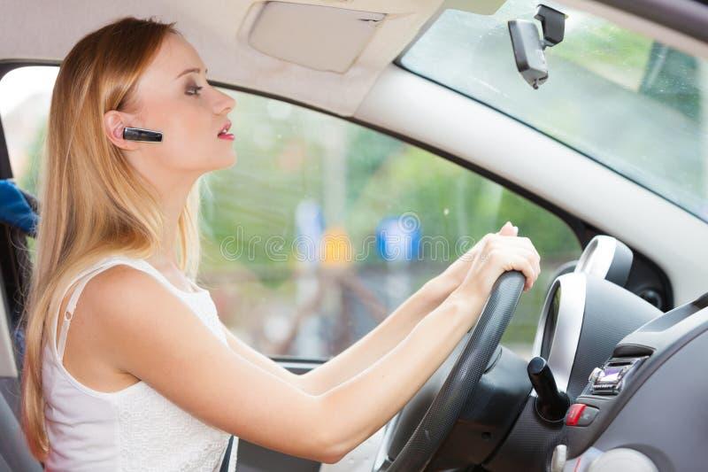 Femme conduisant la voiture avec le casque images stock
