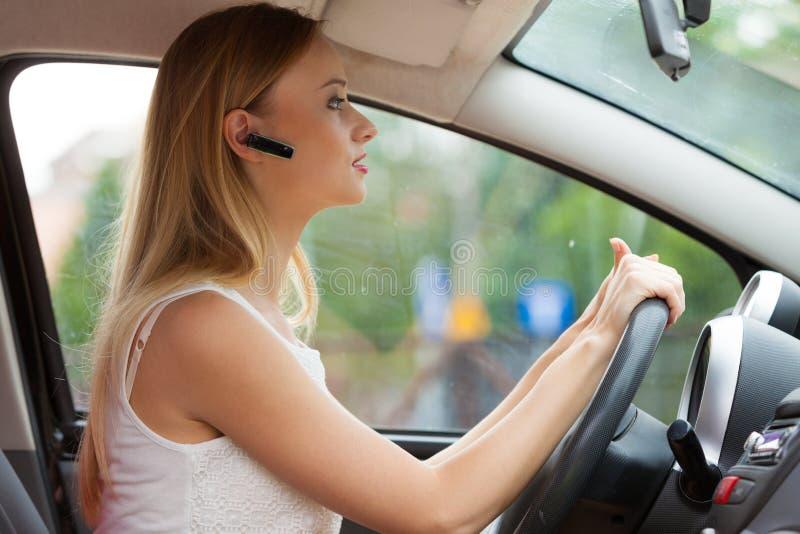Femme conduisant la voiture avec le casque photos stock