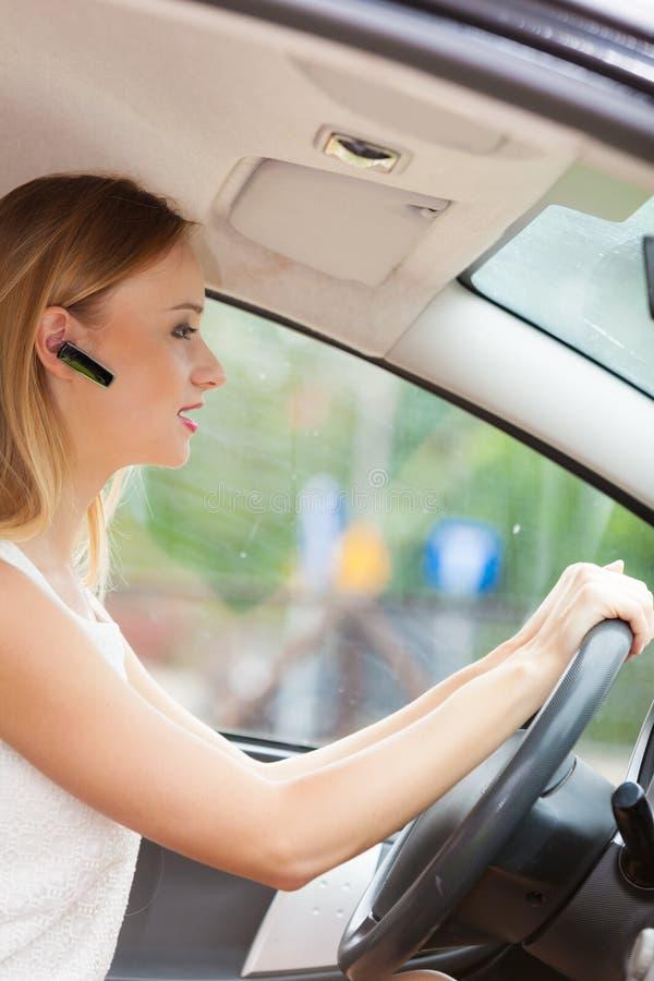 Femme conduisant la voiture avec le casque photographie stock