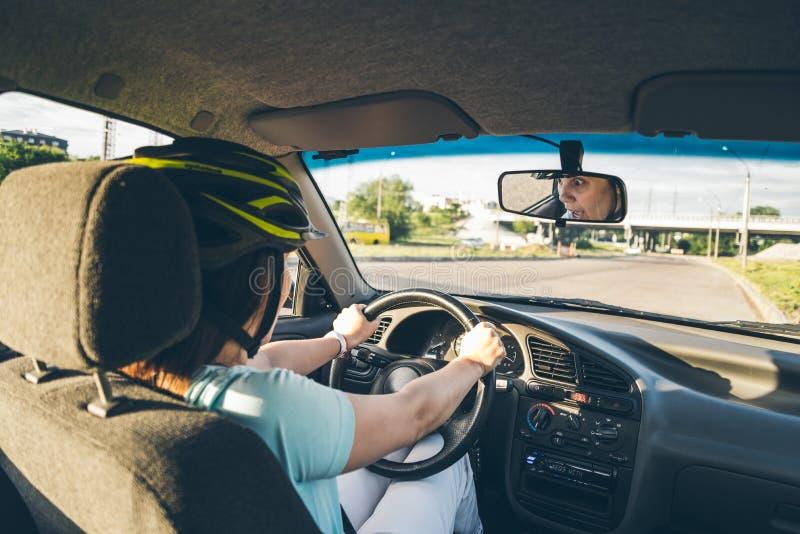 Femme conduisant la voiture dans le casque avec l'horreur sur son visage photo stock