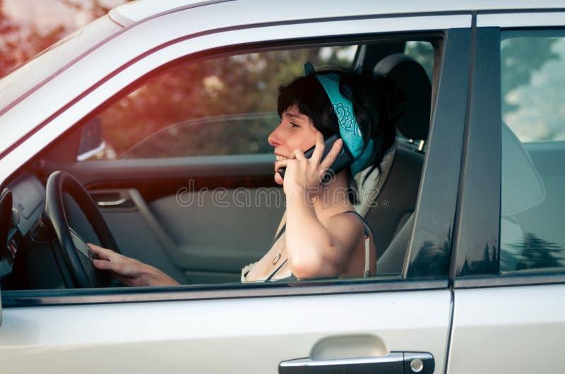 Femme conduisant la voiture et parlant au téléphone image stock