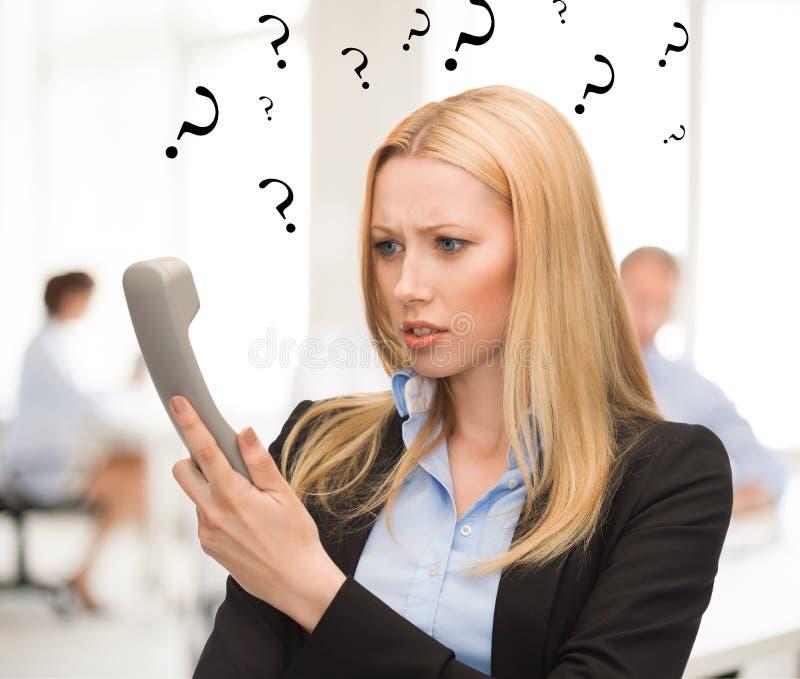 Femme confuse avec le téléphone dans le bureau photo libre de droits