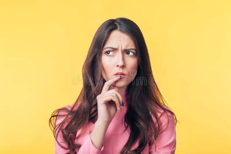 Femme confuse réfléchie regardant parti d'isolement au-dessus du fond jaune photo libre de droits