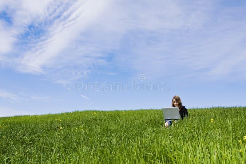 Femme connecté sur l'herbe photographie stock libre de droits
