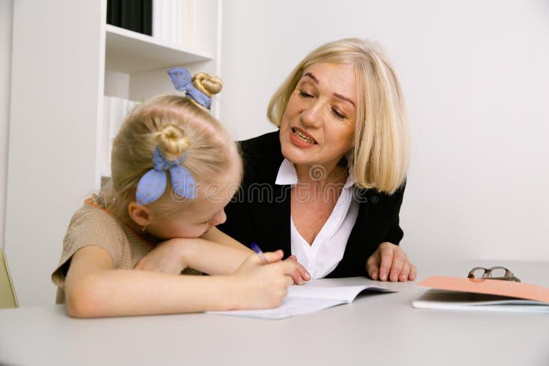 Femme conseillant peu de fille d'int?rieur dans la chambre Psychologue Concept photos libres de droits