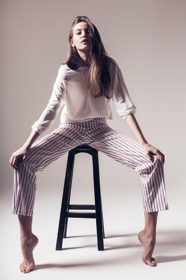 Femme contemporaine dans le pantalon rayé se reposant sur la chaise photos stock