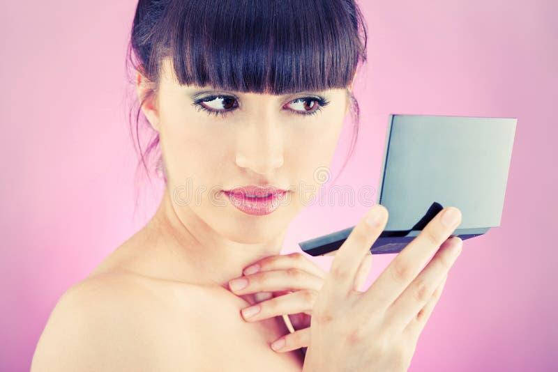 Femme contrôlant la peau de visage dans le miroir photographie stock