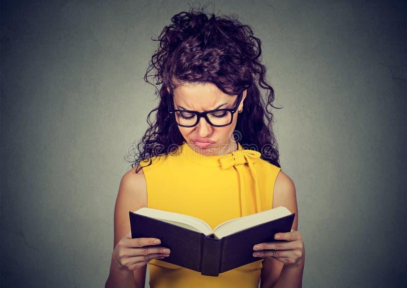 Femme contrariée réfléchie lisant un livre image stock