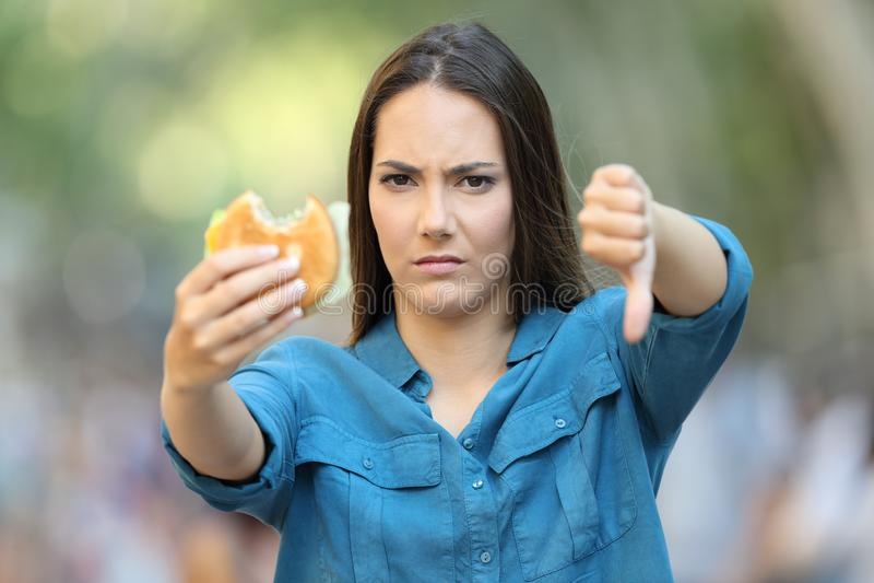 Femme contrariée tenant un hamburger avec le pouce vers le bas photos libres de droits