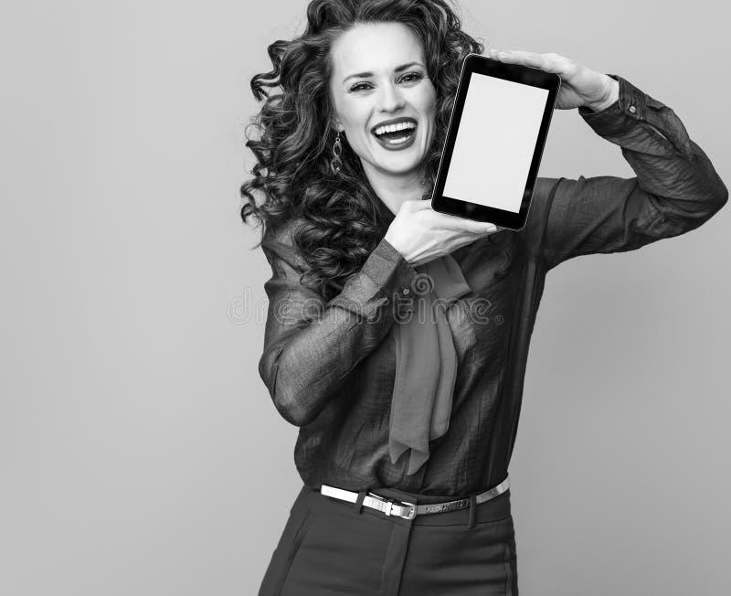 Femme contre l'écran vide de tablette d'apparence de fond photo stock