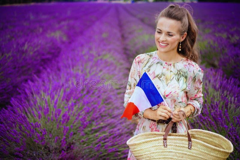 Femme contre le gisement de lavande avec le sac de paille et le drapeau français images stock