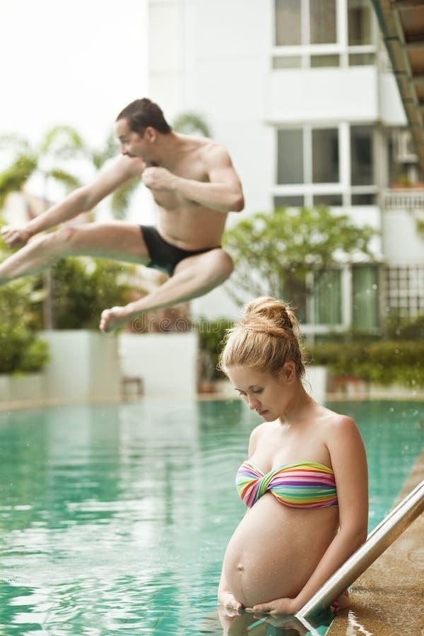 Femme contre son mari sautant dans la piscine photo stock