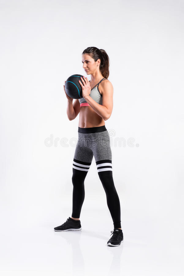 Femme convenable dans l'habillement de sports tenant le medicine-ball, tir de studio photos stock