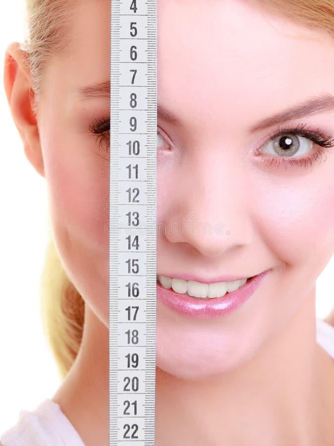 Femme convenable de fille de forme physique couvrant son oeil de bande de mesure photo stock