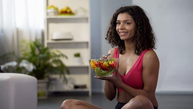 Femme convenable de jeunes mangeant de la salade végétale, se reposant sur le plancher dans l'équipement de gymnase, suivant un r photo libre de droits