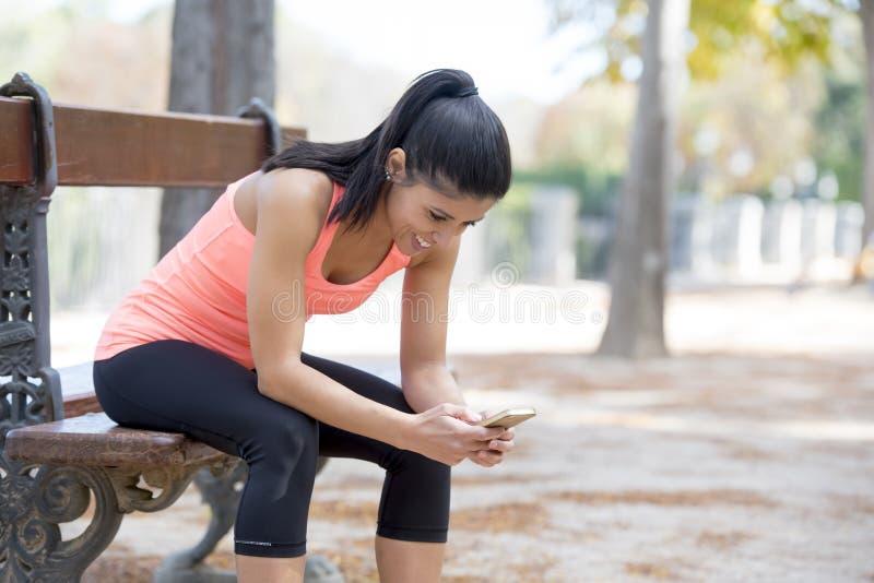Femme convenable de sport regardant la performance de cheminement de l'Internet APP de téléphone portable après la séance d'entra photographie stock libre de droits