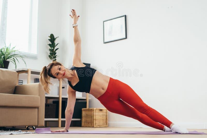 Femme convenable faisant l'exercice de planche à la maison photo libre de droits