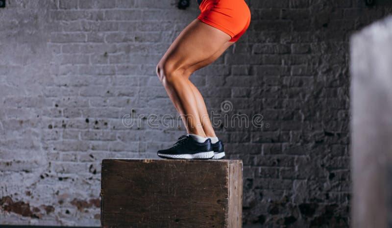 Femme convenable faisant l'exercice de saut de boîte La femme musculaire faisant la boîte saute au gymnase photo libre de droits