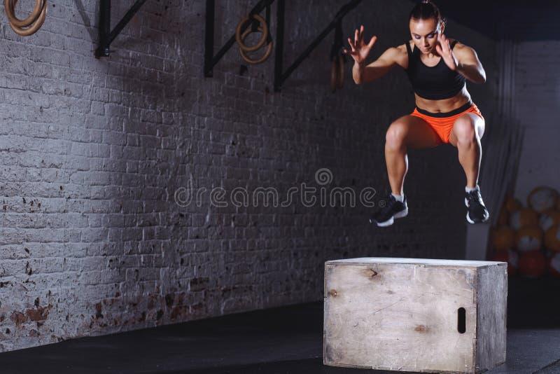 Femme convenable faisant l'exercice de saut de boîte La femme musculaire faisant la boîte saute au gymnase photos stock