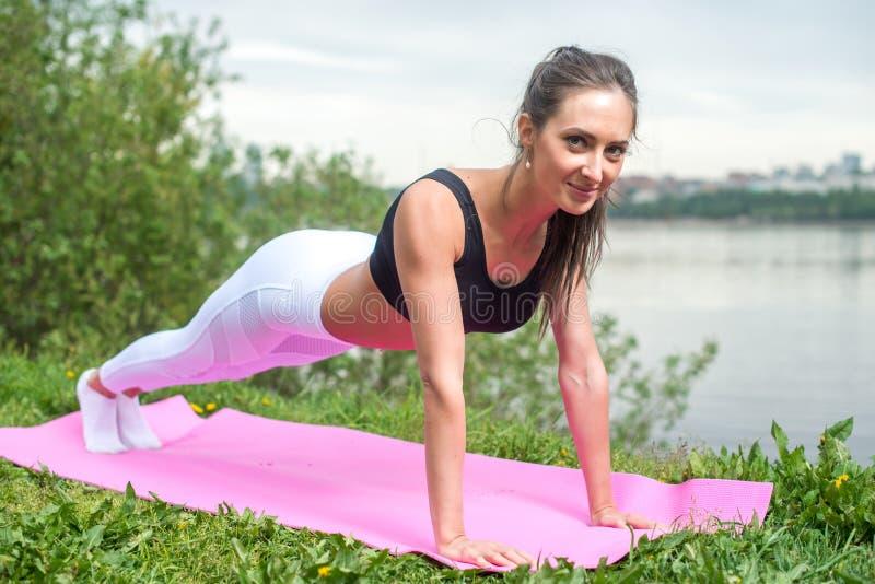 Femme convenable faisant la pleine formation de forme physique d'exercice de noyau de planche établissant dehors photographie stock libre de droits