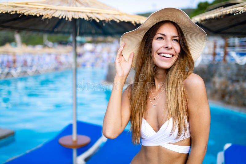 Femme convenable heureuse dans le bikini et chapeau de soleil sur la plage de mer photographie stock