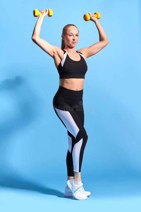 Femme convenable mince dans les vêtements de sport à la mode soulevant des haltères photographie stock