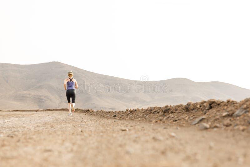 Femme convenable pulsant dans le chemin de terre de désert de distance photographie stock libre de droits