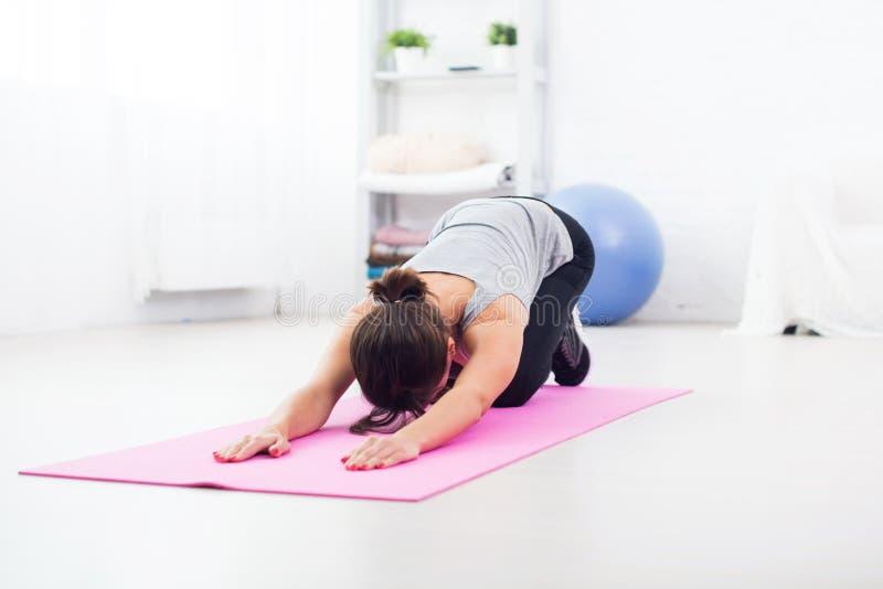 Femme convenable se pliant plus de sur le tapis faisant des pilates images stock